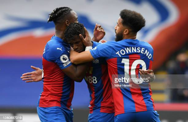 Wilfried Zaha of Crystal Palace celebrates with teammate Michy Batshuayi and Andros Townsend after scoring his team's first goal during the Premier...