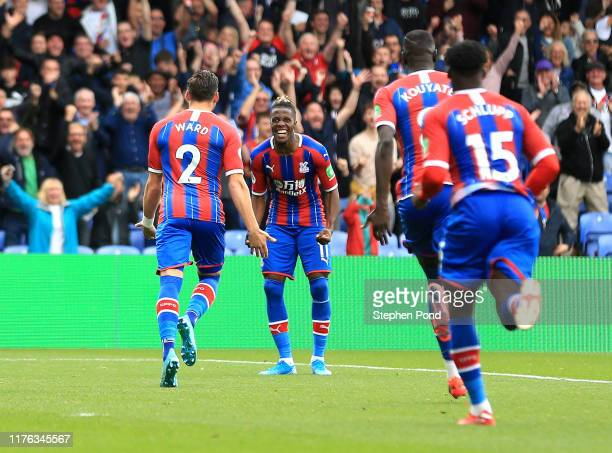 Wilfried Zaha of Crystal Palace celebrates with teammates after after an own goal by Leander Dendoncker of Wolverhampton Wanderers during the Premier...