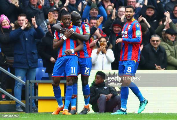 Wilfried Zaha of Crystal Palace celebrates with teammates after he scores his sides first goal during the Premier League match between Crystal Palace...