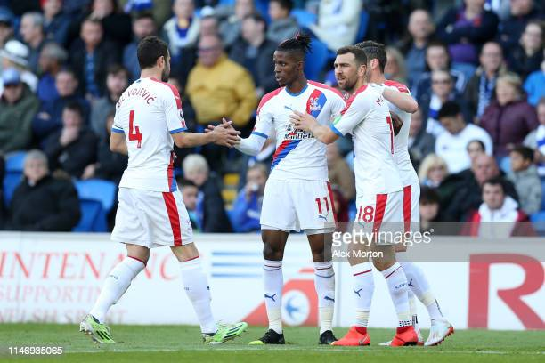 Wilfried Zaha of Crystal Palace celebrates with teammates after scoring his team's first goal during the Premier League match between Cardiff City...