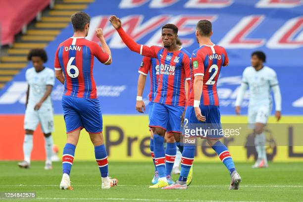 Wilfried Zaha of Crystal Palace celebrates with teammates after scoring his team's first goal during the Premier League match between Crystal Palace...