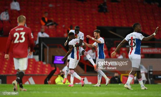 Wilfried Zaha of Crystal Palace celebrates with teammates after scoring his team's third goal during the Premier League match between Manchester...