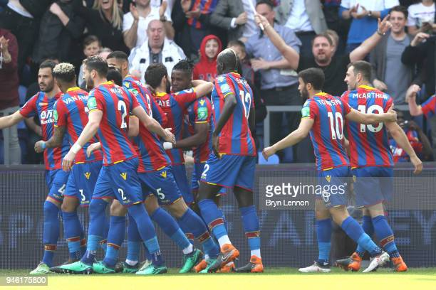 Wilfried Zaha of Crystal Palace celebrates with teammates after scoring his sides first goal during the Premier League match between Crystal Palace...