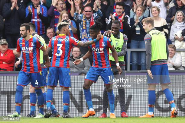 Wilfried Zaha of Crystal Palace celebrates with teammates after scoring his sides third goal during the Premier League match between Crystal Palace...