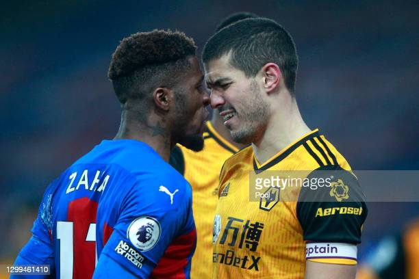 Wilfried Zaha of Crystal Palace clashes with Conor Coady of Wolverhampton Wanderers during the Premier League match between Crystal Palace and...
