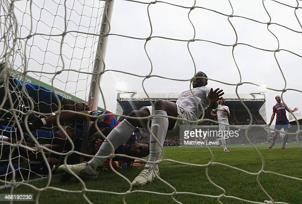 Wilfried Zaha of Crystal Palace collides with the post with Jason Puncheon after Zaha scored the opening goal during the Barclays Premier League...