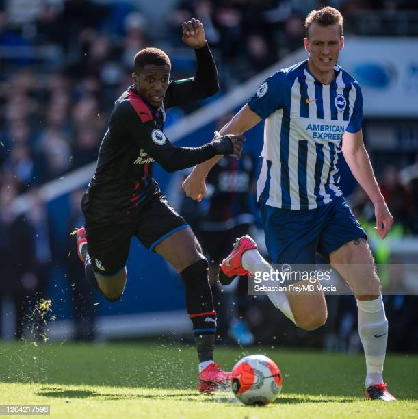 Wilfried Zaha of Crystal Palace competes for the ball with Dan Burn of Brighton Hove Albion during the Premier League match between Brighton Hove...