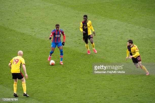 Wilfried Zaha of Crystal Palace control ball around Will Hughes Kiko Femenia Ismaila Sarr of Watford FC during the Premier League match between...