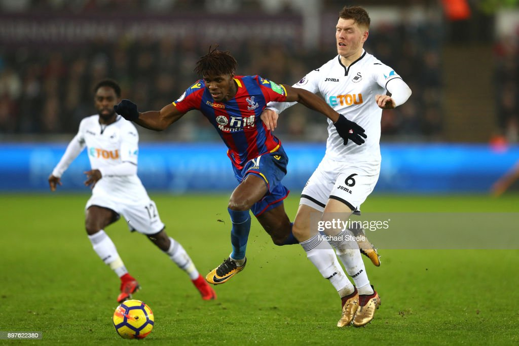 Wilfried Zaha of Crystal Palace escapes a challenge from Alfie Mawson of Swansea City during the Premier League match between Swansea City and Crystal Palace at Liberty Stadium on December 23, 2017 in Swansea, Wales.