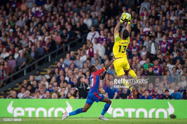 Wilfried Zaha of Crystal Palace fights for the ball with Alisson Becker goalkeeper of Liverpool during the Premier League match between Crystal...