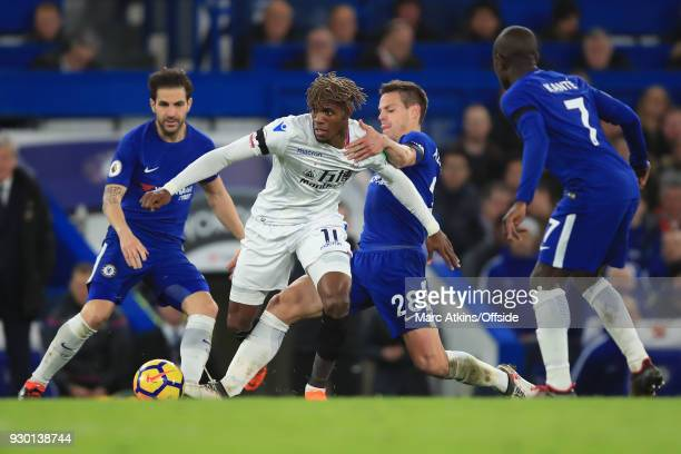 Wilfried Zaha of Crystal Palace in action with Cesc Fabregas Cesar Azpilicueta and N'Golo Kante of Chelsea during the Premier League match between...