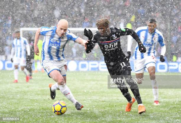 Wilfried Zaha of Crystal Palace is challenged by Aaron Mooy of Huddersfield Town during the Premier League match between Huddersfield Town and...