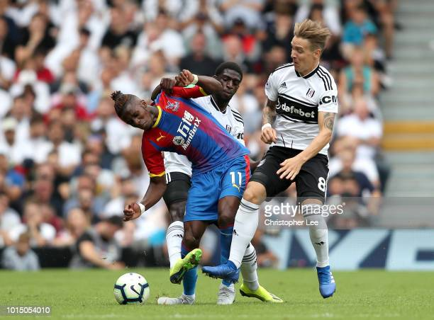 Wilfried Zaha of Crystal Palace is challenged by Aboubakar Kamara of Fulham and Stefan Johansen of Fulham during the Premier League match between...