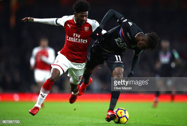Wilfried Zaha of Crystal Palace is challenged by Ainsley MaitlandNiles of Arsenal during the Premier League match between Arsenal and Crystal Palace...