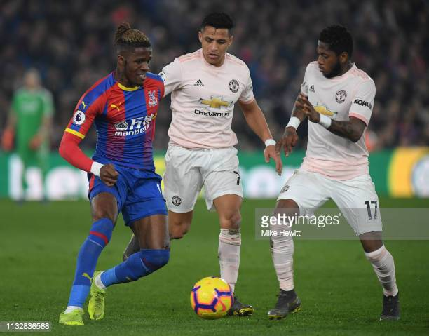 Wilfried Zaha of Crystal Palace is challenged by Alexis Sanchez and Fred of Manchester United during the Premier League match between Crystal Palace...