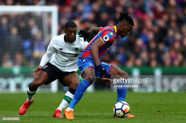 Wilfried Zaha of Crystal Palace is challenged by Georginio Wijnaldum of Liverpool during the Premier League match between Crystal Palace and...
