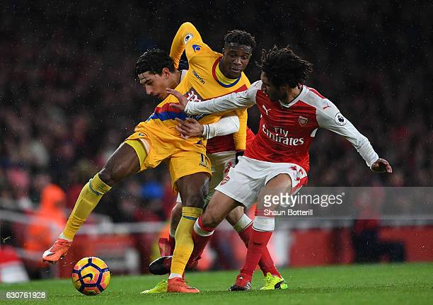 Wilfried Zaha of Crystal Palace is challenged by Hector Bellerin and Mohamed Elneny of Arsenal during the Premier League match between Arsenal and...