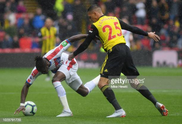 Wilfried Zaha of Crystal Palace is challenged by Jose Holebas of Watford during the Premier League match between Watford FC and Crystal Palace at...