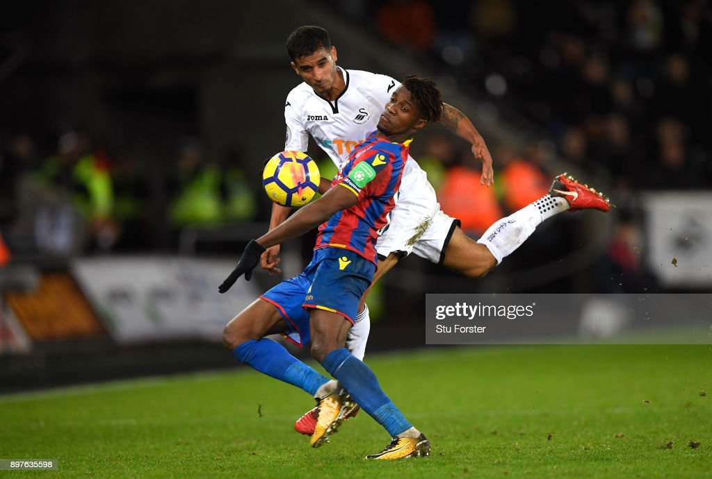 Wilfried Zaha of Crystal Palace is challenged by Kyle Naughton of Swansea City during the Premier League match between Swansea City and Crystal Palace at Liberty Stadium on December 23, 2017 in Swansea, Wales.