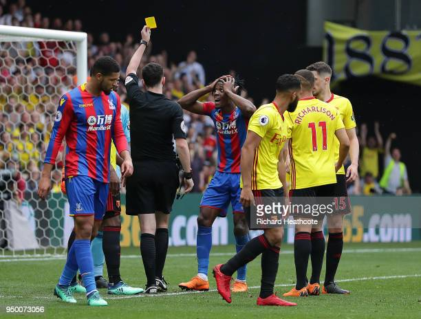 Wilfried Zaha of Crystal Palace is shown yellow card by referee Chris Kavanagh during the Premier League match between Watford and Crystal Palace at...