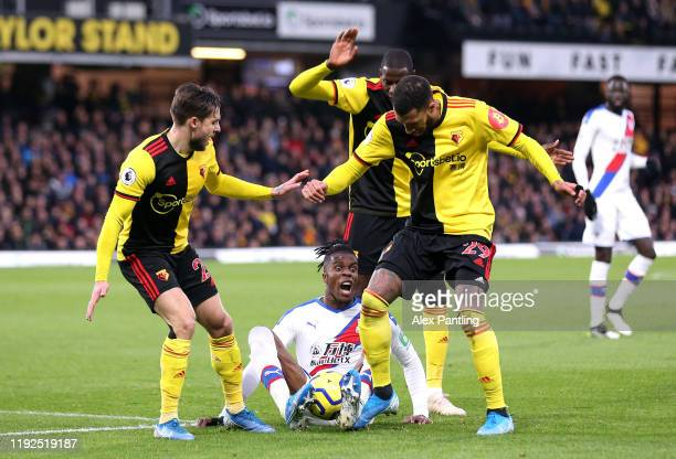 Wilfried Zaha of Crystal Palace is surrounded by Kiko Femina and Etienne Capoue of Watford during the Premier League match between Watford FC and...