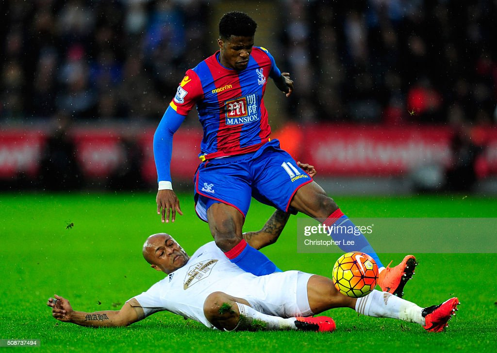 Wilfried Zaha of Crystal Palace is tackled by Andre Ayew of Swansea City during the Barclays Premier League match between Swansea City and Crystal Palace at the Liberty Stadium on February 6, 2016 in Swansea, Wales.