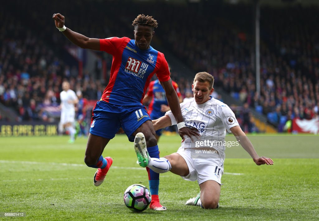Wilfried Zaha of Crystal Palace (L) is tackled by Marc Albrighton of Leicester City (R) during the Premier League match between Crystal Palace and Leicester City at Selhurst Park on April 15, 2017 in London, England.