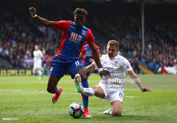 Wilfried Zaha of Crystal Palace is tackled by Marc Albrighton of Leicester City during the Premier League match between Crystal Palace and Leicester...