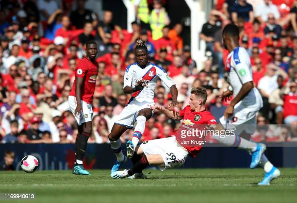 Wilfried Zaha of Crystal Palace is tackled by Scott McTominay of Manchester United during the Premier League match between Manchester United and...