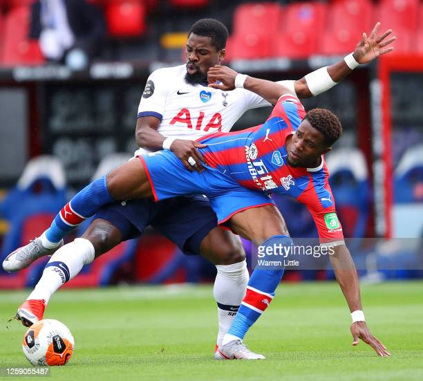 Wilfried Zaha of Crystal Palace is tackled by Serge Aurier of Tottenham Hotspur during the Premier League match between Crystal Palace and Tottenham...