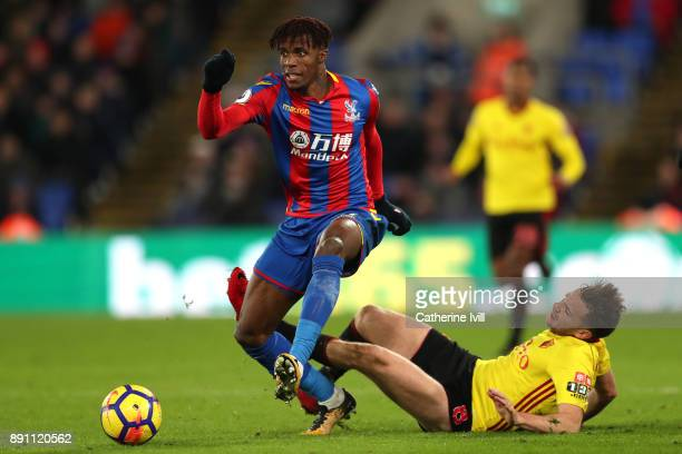 Wilfried Zaha of Crystal Palace is tackled by Tom Cleverley of Watford during the Premier League match between Crystal Palace and Watford at Selhurst...