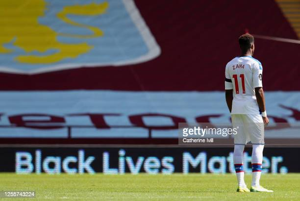 Wilfried Zaha of Crystal Palace looks on as a Black Lives Matter movement board is seen during the Premier League match between Aston Villa and...