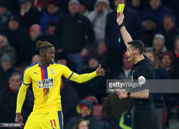 Wilfried Zaha of Crystal Palace reacts to Match Referee Andre Marriner after being shown a yellow card which leads to his sendingoff during the...
