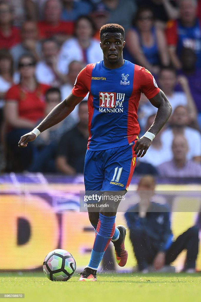 Wilfried Zaha of Crystal Palace runs with the ball during the Premier League match between Crystal Palace and Bournemouth at Selhurst Park on August 27, 2016 in London, England.
