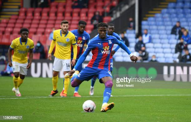 Wilfried Zaha of Crystal Palace scores a penalty for his team's first goal during the Premier League match between Crystal Palace and Brighton & Hove...