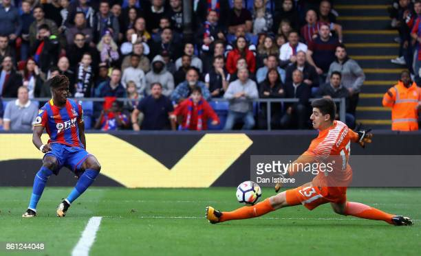 Wilfried Zaha of Crystal Palace scores his sides second goal past Thibaut Courtois of Chelsea during the Premier League match between Crystal Palace...