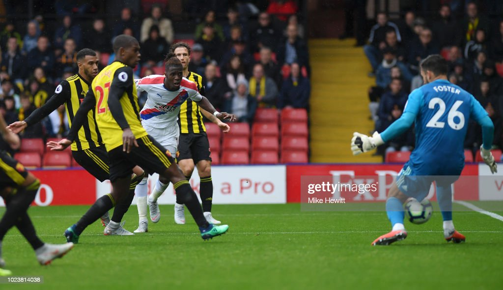 Wilfried Zaha of Crystal Palace scores his team's first goal past Ben Foster of Watford during the Premier League match between Watford FC and Crystal Palace at Vicarage Road on August 26, 2018 in Watford, United Kingdom.