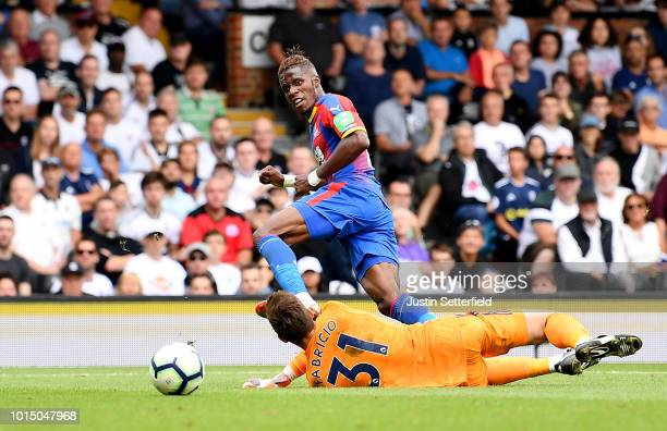 Wilfried Zaha of Crystal Palace scores his team's second goal past Fabricio Agosto Ramirez of Fulham during the Premier League match between Fulham...