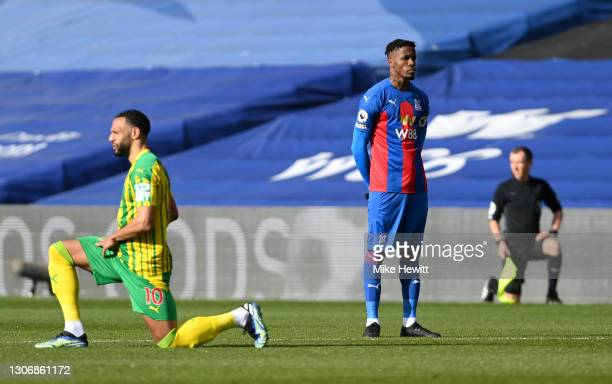 Wilfried Zaha of Crystal Palace stands at kick off as Matt Phillips of West Bromwich Albion takes a knee in support of the Black Lives Matter...