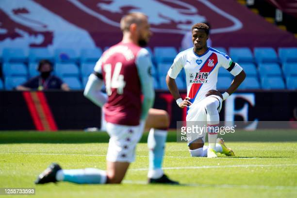 Wilfried Zaha of Crystal Palace takes a knee in support of the Black Lives Matter movement prior to during the Premier League match between Aston...