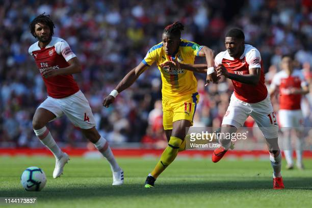 Wilfried Zaha of Crystal Palace takes on Ainsley MaitlandNiles and Mohamed Elneny of Arsenal during the Premier League match between Arsenal FC and...