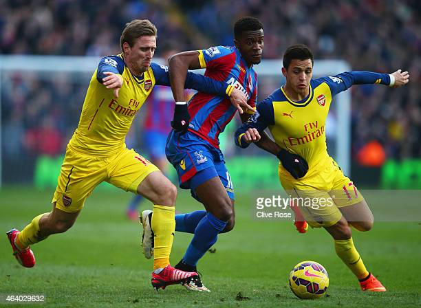 Wilfried Zaha of Crystal Palace takes on Alexis Sanchez and Nacho Monreal of Arsenal during the Barclays Premier League match between Crystal Palace...