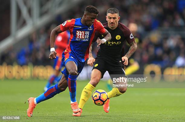 Wilfried Zaha of Crystal Palace takes the ball past Aleksander Kolorov of Manchester City during the Premier League match between Crystal Palace and...