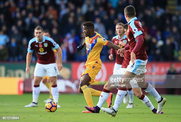 Wilfried Zaha of Crystal Palace takes the ball past some Burnley defenders during the Premier League match between Burnley and Crystal Palace at Turf...