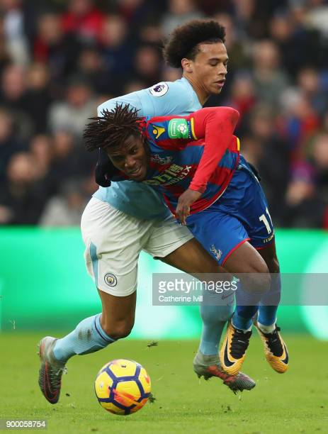 Wilfried Zaha of Crystal Palace tangles with Leroy Sane of Manchester City during the Premier League match between Crystal Palace and Manchester City...