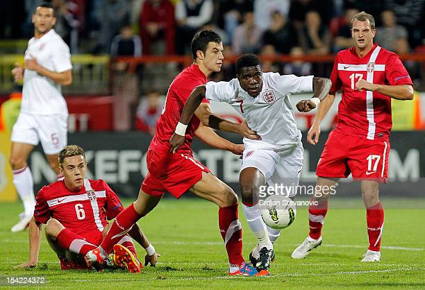 Wilfried Zaha of England is challenged by Luka Milivojevic of Serbia during the Under 21 European Championship Play Off second leg match between...