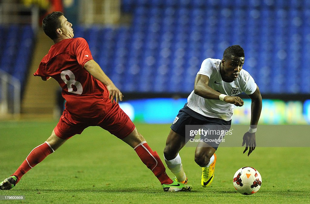 Wilfried Zaha of England (R) is tackled by Vadim Rata of Moldova during the 2015 UEFA European U21 Championships Qualifier between England U21 and Moldova U21 at The Madejski Stadium on September 05, 2013 in Reading, England,