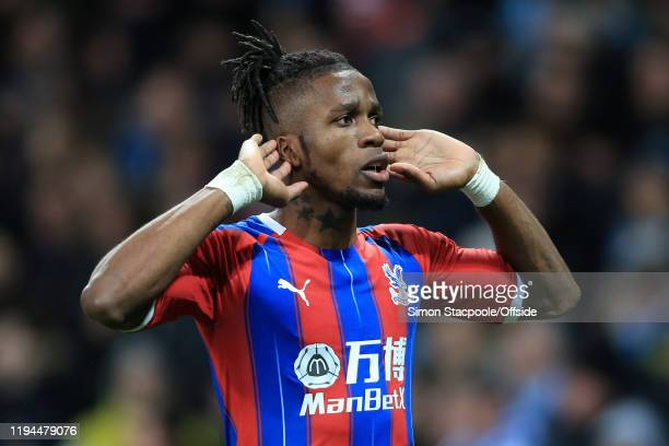 Wilfried Zaha of Palace cups his ears as he celebrates after scoring their 2nd goal during the Premier League match between Manchester City and...