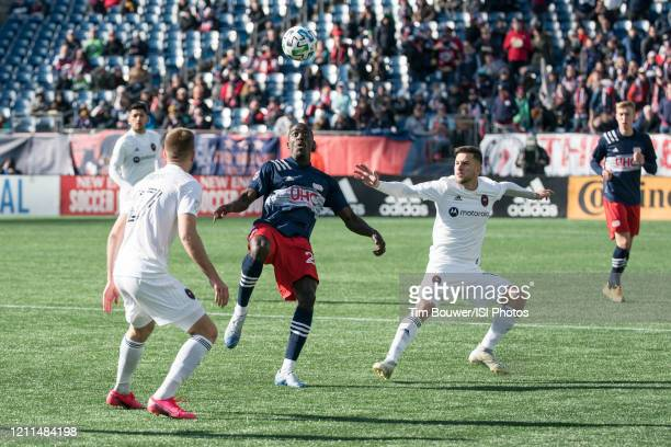 Wilfried Zahibo of New England Revolution prepares for a high ball as Robert Beric of Chicago Fire and Alvaro Medran of Chicago Fire close in during...