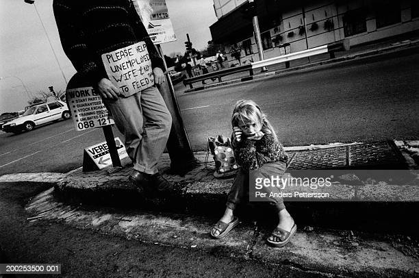 Wilhelm Fourie an unemployed man begs with his daughter Bianca on September 22 1998 at a busy intersection in Cresta Johannesburg South Africa Mr...